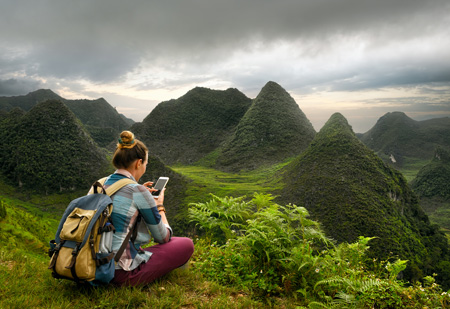 student hiking in mountains with backpack and phone